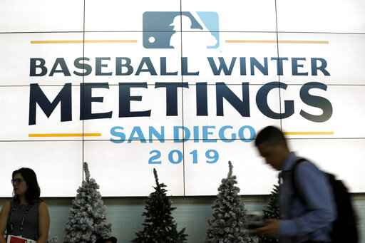 People pass a display during the Major League Baseball winter meetings Monday, Dec. 9, 2019, in San Diego. (AP Photo/Gregory Bull)