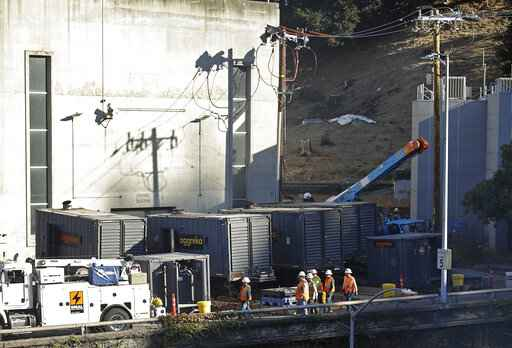 Crews work to connect generators in effort to keep the Caldecott Tunnel open to traffic during a possible power outage at noon on Wednesday, Oct. 9, 2019, in Oakland, Calif. Pacific Gas & Electric has cut power to more than half a million customers in Northern California hoping to prevent wildfires during dry, windy weather throughout the region. (AP Photo/Ben Margot)