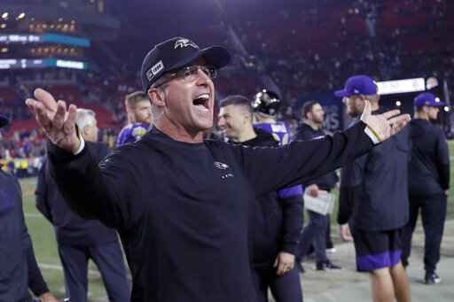 FILE - Baltimore Ravens head coach John Harbaugh celebrates after beating the Los Angeles Rams in an NFL football game  in Los Angeles, in this Nov. 25, 2019, file photo. Home-field advantage in the playoffs is overrated for Ravens coach John Harbaugh, who has found that the road to success in the postseason usually involves packing his bags and getting the heck out of Baltimore. Last week's 20-13 victory in Tennessee was Harbaugh's eighth on the road in the playoffs, the most by any coach in NFL history, breaking a tie with Tom Landry and Tom Coughlin. (AP Photo/Marcio Jose Sanchez, FIle)