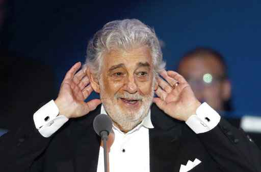 FILE - In this Aug. 28, 2019, file photo, Opera star Placido Domingo listens to applause at the end of a concert in Szeged, Hungary. Despite objections from sexual abuse activists, the Israeli Opera will host a week-long singing competition organized by Domingo in Tel Aviv later this year. Domingo has withdrawn from all U.S. performances since reports by The Associated Press last year detailed accusations of sexual harassment or other inappropriate, sexually charged conduct.  (AP Photo/Laszlo Balogh, File)