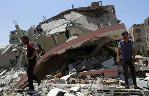 People walk amid the rubble of a destroyed residential building which was hit by Israeli airstrikes, in Gaza City, Wednesday, May 12, 2021. (AP Photo/Adel Hana)