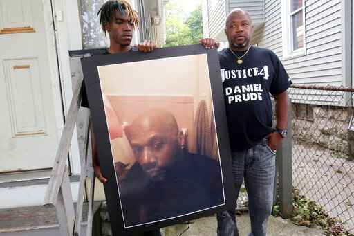 FILE - In this Sept. 3, 2020 file photo, Joe Prude, brother of Daniel Prude, right, and his son Armin, stand with a picture of Daniel Prude in Rochester, N.Y. Newly released transcripts show that a grand jury investigating the police suffocation death of Daniel Prude last year in Rochester, New York, voted 15-5 to clear the three officers involved in his restraint of a criminally negligent homicide charge sought by prosecutors. (AP Photo/Ted Shaffrey, File)