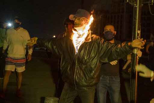 A Lebanese activist tries to set himself on fire in protest after security forces ask protesters who have been holding a sit-in in Martyrs Square, to dismantle their tents and go home in line with a nighttime curfew imposed by the government to help stem the spread of the coronavirus in Beirut, Lebanon, Friday, March 27, 2020. The new coronavirus causes mild or moderate symptoms for most people, but for some, especially older adults and people with existing health problems, it can cause more severe illness or death. (AP Photo/Hassan Ammar)