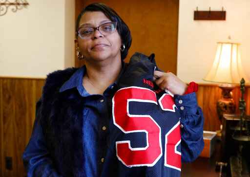 FILE- In this Feb. 13, 2019 file photo, JoAnne Atkins-Ingram drapes her son, Braeden Bradforth's old Neptune High School football jersey over her shoulder in her attorney's office in Avon-by-the-Sea, N.J. A Kansas community college has reached a settlement with Bradforth's family on Friday, July 31, 2020, for the 19-year-old's death from heatstroke after football conditioning drills n August 2018. (Doug Hood/The Asbury Park Press via AP)