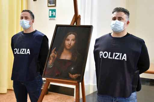 Italian police officers stand by a copy of the