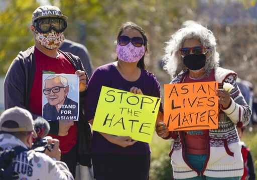 A man holds a portrait of late Vichar Ratanapakdee, left, a 84-year-old immigrant from Thailand, who was violently shoved to the ground in a deadly attack in San Francisco, during a community rally to raise awareness of anti-Asian violence and racist attitudes, in response to the string of violent racist attacks against Asians during the pandemic, held at Los Angeles Historic Park near the Chinatown district in Los Angeles, Saturday, Feb. 20, 2021. (AP Photo/Damian Dovarganes)