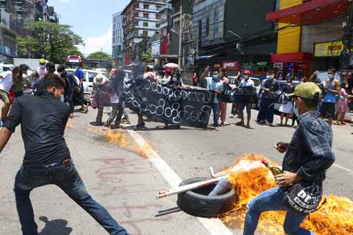 Anti-coup protesters burn tires and chant slogans with banner read ''The Kamayut strike will be fight for to the end when we get victory