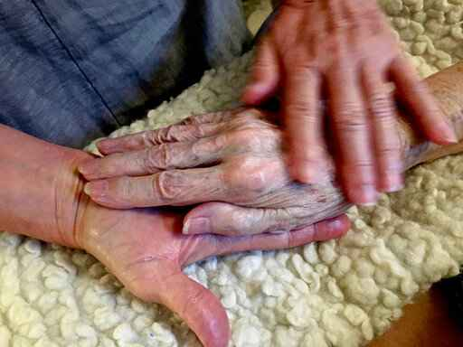 In this 2016 photo provided by Thomas Marrinson, Allison Beach holds the hand of her ailing mother Kathryne Beach inside her home in Hinesburg, Vt. Allison Beach and her husband struggled to figure out how to get help for her mother, who lived with them for three years before dying at their home Hinesburg, Vermont, in 2016. The experience led Beach, who was a nurse, to seek special training in end-of-life care and has become a doula, hoping to help others in such circumstances.  (Thomas Marrinson via AP)