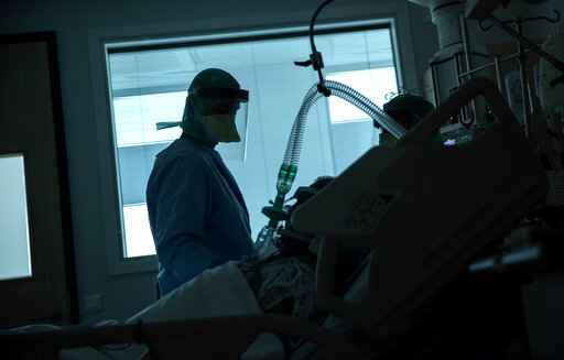 FILE - In this March 27, 2020, file photo, a health worker in the intensive care ward observes a COVID-19 patient at a hospital in Belgium. Experts say Europe has some of the world's best health systems, but many hospitals have been overwhelmed with coronavirus patients and are ill-equipped to handle the pandemic. (AP Photo/Francisco Seco, File)