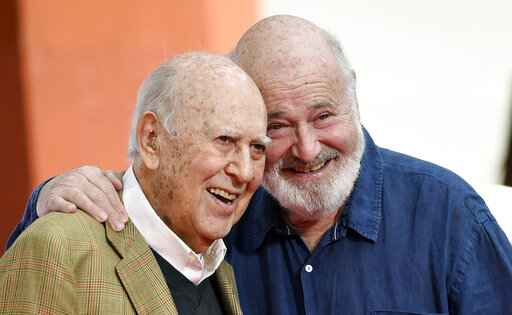 FILE - In this April 7, 2017 file photo, Carl Reiner, left, and his son Rob Reiner pose together following their hand and footprint ceremony at the TCL Chinese Theatre in Los Angeles. Carl Reiner, the ingenious and versatile writer, actor and director who broke through as a