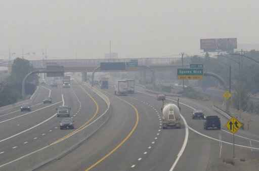 FILE - In this Wednesday, Aug. 19, 2020. file photo, smoke from California wildfires up to 200 miles away obscures the view of traffic traveling on Interstate 80, looking west in Sparks, Nev. Local schools canceled all outdoor activities as the air quality index approached the