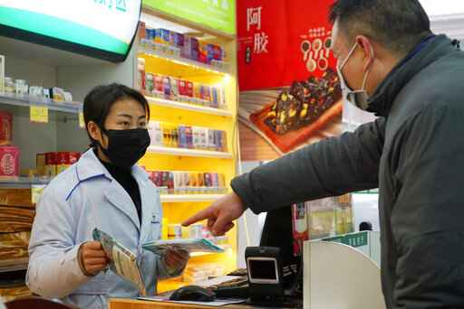 Staff sell masks at a Yifeng Pharmacy in Wuhan, Chin, Wednesday, Jan. 22, 2020. Pharmacies in Wuhan are restricting customers to buying one mask at a time amid high demand and worries over an outbreak of a new coronavirus. The number of cases of the new virus has risen over 400 in China and the death toll to 9, Chinese health authorities said Wednesday. (AP Photo/Dake Kang)