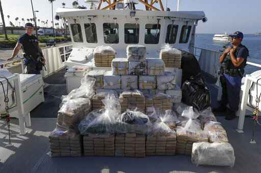 FILE - In this Aug. 29, 2019, file photo, members of the Coast Guard stand near seized cocaine in Los Angeles. The nation's drug addiction crisis has been morphing in a deadly new direction: more Americans struggling with meth and cocaine. Now the government will allow states to use federal money earmarked of the opioid crisis to help people addicted to those drugs as well. The change to a $1.5 billion opioid grants program was buried in a massive spending bill that Congress passed late in 2019. (AP Photo/Chris Carlson, file)