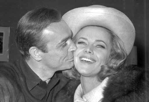 FILE - In this B/W file photo dated March 25, 1964, British actor Sean Connery kisses actress Honor Blackman during a party at Pinewood Film Studios, in Iver Heath, England.  Blackman, the actor best-known for playing Bond girl Pussy Galore, hasdied of natural causes unrelated to coronavirus, aged 94, according to an announcement Monday April 6, 2020. (AP Photo, FILE)