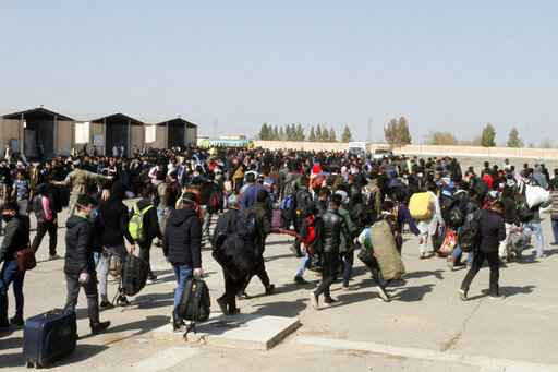 FILE - In this Wednesday, March 18, 2020 file photo, thousands of Afghan refugees walk as they enter Afghanistan at the Islam Qala border crossing with Iran, in the western Herat Province. Some 200,000 Afghans and counting have returned from Iran to their home country after losing their jobs in the coronavirus pandemic or out of fear of getting infected. They are flowing across the border from a country that has one of the world's worst outbreak to an impoverished nation that is woefully unprepared to deal with the virus. (AP Photo/Hamed Sarfarazi, File)