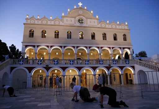 Pilgrims crawl in front of the Holy Church of Panagia of Tinos, on the Aegean island of Tinos, Greece, on Friday, Aug. 14, 2020. For nearly 200 years, Greek Orthodox faithful have flocked to Tinos for the August 15 feast day of the Assumption of the Virgin Mary, the most revered religious holiday in the Orthodox calendar after Easter. But this year there was no procession, the ceremony _ like so many lives across the globe _ upended by the coronavirus pandemic. (AP Photo/Thanassis Stavrakis)