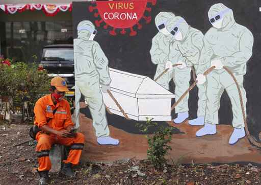 A street sweeper checks his mobile phone as he takes a break near a coronavirus-themed mural in Jakarta, Indonesia, Friday, Aug. 14, 2020. Indonesia's only vaccine production company has started this week a so-called phase 3 clinical trials to test a potential coronavirus vaccine developed by a Chinese company. (AP Photo/Tatan Syuflana)