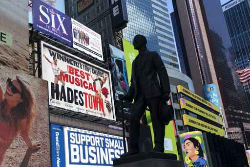 A statue of playwright and performer George M. Cohan stands in New York's Times Square in front of billboards for Broadway shows, Thursday, May 6, 2021. Gov. Andrew Cuomo has announced that Broadway theaters can reopen Sept. 14, 2021. (AP Photo/Mark Lennihan)