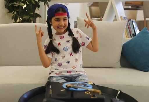 Michelle Rasul flashes a rockstar sign in the lobby of her apartment building in Dubai, United Arab Emirates, Sunday, May 9, 2021. Rasul, a 9-year-old girl from Azerbaijan who lives in Dubai, is scratching her way to the top as a DJ after competing in the DMC World DJ Championship. (AP Photo/Kamran Jebreili)