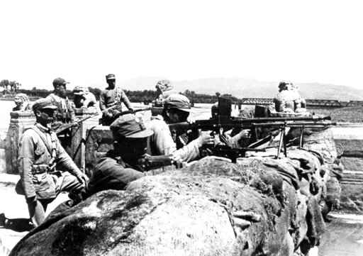FILE - In this July 8, 1937, file photo, members of the Chinese 29th Army defend the city behind a hastily constructed sandbag barricade on the Marco Polo Bridge, 14 miles (22.5 kilometer) southwest of Pieping, China, against Japanese attackers. On July 7, Chinese troops fired on Japanese troops at the Marco Polo bridge, a clash between the two countries that led to the Second Sino Japanese War. The Pacific War was so massive and so calamitous that it can be difficult to put it in context. There was the Marco Polo Bridge Incident that triggered the Sino-Japanese War, the Battle of Midway that changed the course of the war and the dramatic flag-raising on Iwo Jima. (AP Photo/File)