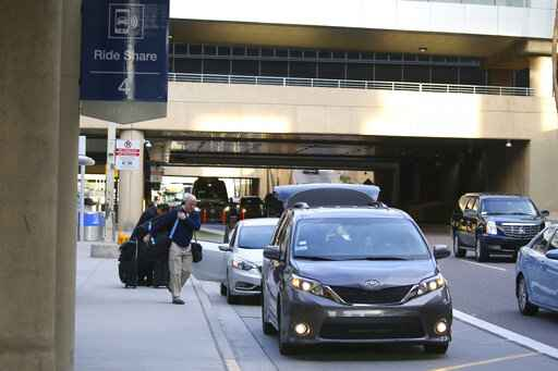 FILE - In this Dec. 18, 2019, file photo passengers find their rides at the Ride Share point as they exit Phoenix Sky Harbor International Airport in Phoenix. The Arizona Supreme Court has unanimously ruled that the Phoenix airport can raise fees for Uber and Lyft to pick up and drop off customers. The ride-hailing companies have threatened to stop serving the airport over the $4 pickup and drop-off fees. The court on Thursday, April 2, 2020 rejected a complaint filed by Republican Attorney General Mark Brnovich, who said the fee hikes are