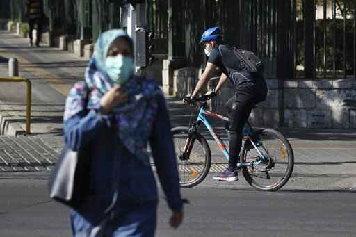 Wearing protective face masks to help prevent the spread of the coronavirus, a man rides his bicycle and a woman crosses a street in downtown Tehran, Iran, Monday, April 5, 2021. Iran's capital is once again under a code red status, the highest level of restrictions imposed to curb the spread of the coronavirus as the country struggles with a new surge in daily deaths. (AP Photo/Vahid Salemi)