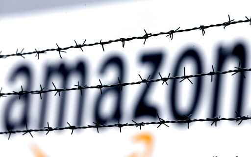 FILE - In this Feb. 19, 2013 file photo, the internet trader Amazon logo is seen behind barbed wire at the company's logistic center in Rheinberg, Germany. A European Union court annulled Wednesday, May 12, 2021 a ruling by the European Commission that a tax deal between the Luxembourg government and Amazon amounted to illegal state support. The Commission's decision related to Luxembourg's tax treatment of two companies in the Amazon group, Amazon EU and Amazon Europe Holding Technologies. (AP Photo/Frank Augstein, File)
