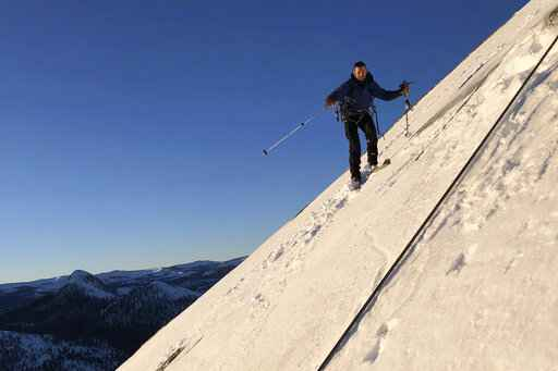 In this photo provided by Jason Torlano, Zach Milligan is shown on his descent down Half Dome in Yosemite National Park, Calif., on Sunday, Feb.  21, 2021. Two men climbed some 4,000 feet to the top of Yosemite's Half Dome in subfreezing temperatures and skied down the famously steep monolith to the valley floor. Jason Torlano, 45, and Zach Milligan, 40, completed the daring descent in five hours on Sunday by charging down Half Dome's arching back and using ropes to rappel down several sections of bare rock known as the