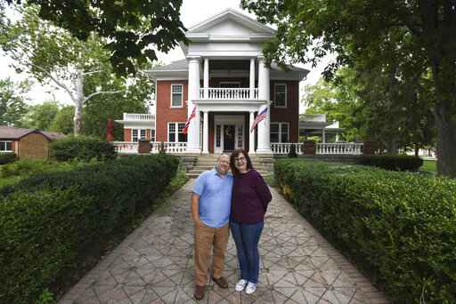This July 2020 photo shows Kjersten and Greg Offenecker, the owners of a Civil War-era mansion turned bed and�breakfast in St. Johns, Mich.   The owners of the bed and breakfast have removed a Norwegian flag outside of their business after being accused of promoting racism from people who think that it is a Confederate flag.  Kjersten and Greg Offenecker, owners of The Nordic Pineapple, hung the flag opposite of the American flag after they moved into the Civil War-era mansion in 2018. The red flag, with a blue cross superimposed on a white cross, is a nod to Kjersten Offenbecker's grandfather, who was born in Norway.  (Matthew Dae Smith/Lansing State Journal via AP)