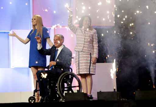 File - In this June 15, 2018 file photo, Texas Gov. Greg Abbott, center, with wife, Cecilia, right, and daughter, Audrey, at the Texas GOP Convention, in San Antonio. As the Texas GOP presses ahead with plans for a July convention amid a worsening coronavirus outbreak, the state's largest medical group Tuesday June 30, 2020, urged the party to reconsider before thousands of Republican activists flock to Houston, which has become one of the nation's most troubling hotspots. (AP Photo/Eric Gay File)