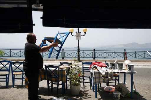 FILE - In this Wednesday, May 20, 2020 file photo, a worker places chairs at a fish restaurant ahead of its reopening in Piraeus, near Athens. Greece's Prime Minister Kyriakos Mitsotakis said Wednesday April 21, 2021, the country's tourism industry will open on May 15 when a ban on travel between different regions in the country will be lifted, adding that restaurants and cafes will also be allowed to reopen outdoor areas starting on May 3. (AP Photo/Thanassis Stavrakis, File)