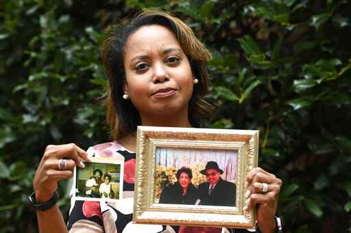 In this Sept. 6, 2019, photo, Donna Cryer holds up family photos that include her father Roland Henry, as she poses for a photo in Washington. When her father died, she tried to donate his organs, yet the local organ collection agency said no, without talking to the family or providing a reason.