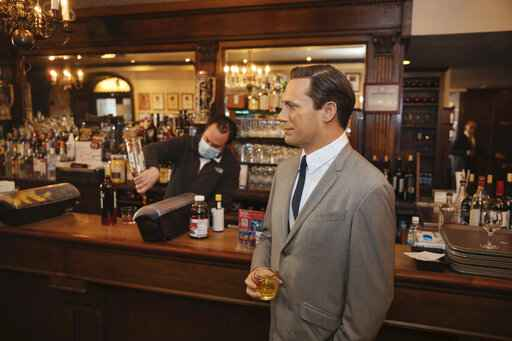 A wax statue of actor John Hamm stands by the bar with a drink at Peter Luger Steakhouse on Friday, Feb, 26, 2021, in New York. The statue, on loan from Madame Tussauds, will help fill out the restaurant during COVID-19 occupancy restrictions. (AP Photo/Kevin Hagen)