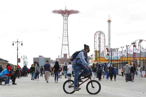 A young man wearing a protective face mask rides his bicycle along a fairly crowded Coney Island boardwalk during the current coronavirus outbreak, the afternoon of Sunday, May 24, 2020, in New York. No swimming was allowed and social distancing reminders were abundant on the beach as Memorial Day weekend kicked off the first weekend of summer. (AP Photo/Kathy Willens)