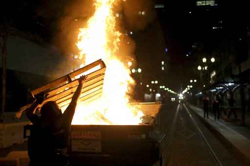Protesters light a fire in a dumpster in downtown Portland, Ore., Friday, April 16, 2021. Police in Portland, said Saturday they arrested several people after declaring a riot Friday night when protesters smashed windows, burglarized businesses and set multiple fires during demonstrations that started after police fatally shot a man while responding to reports of a person with a gun. (Dave Killen/The Oregonian via AP)