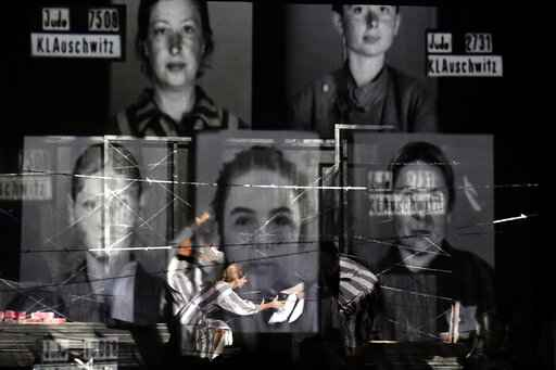 Portraits of Auschwitz death camp prisoners are displayed on a mesh as actresses of the Jewish State Theatre, perform during the premiere of the