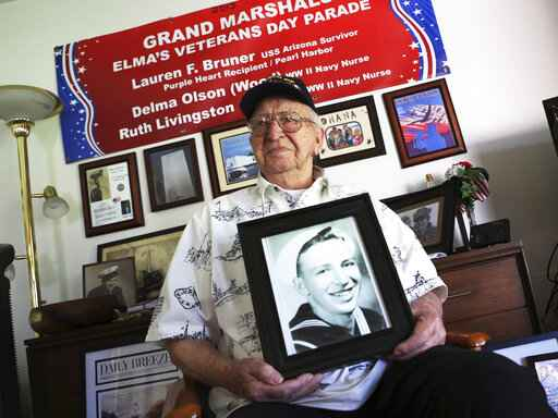 FILE - In this Nov. 17, 2016, file photo, Lauren Bruner, a survivor of the USS Arizona which was attacked on Dec. 7, 1941, holds with a 1940 photo of himself at his home in La Mirada, Calif. Divers will place the ashes of Bruner in the wreckage of his ship during a ceremony this weekend in Pearl Harbor, Hawaii.   Bruner died earlier in 2019 at the age of 98. (AP Photo/Reed Saxon, File)