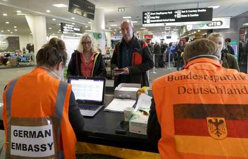 Foreign tourists wait to be checked by German Embassy staff at Christchurch Airport terminal as they prepare to check in for a charter flight back to Germany via Vancouver from Christchurch, New Zealand, Monday, April 6, 2020. The German Embassy in Wellington last week said more than 12,000 German tourists had signed up for its repatriation program from New Zealand following the strict monthlong lockdown, which is aimed at preventing more coronavirus infections. The new coronavirus causes mild or moderate symptoms for most people, but for some, especially older adults and people with existing health problems, it can cause more severe illness or death. (AP Photo/Mark Baker)