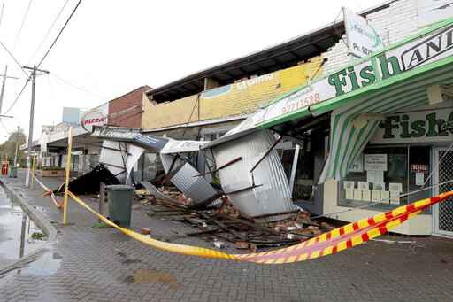 Debris falls from a row of damaged shops in Perth, Australia, Monday, May 25, 2020. There are reports of damage to buildings, homes, fences, electricity infrastructure and trees across Perth as a severe storm hit the coast and brought wind gusts of more than 100 kilometers (60 miles) per hour, officials said. (Richard Wainwright/AAP Image via AP)