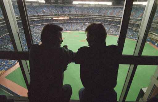 FILE - In this Oct. 22, 1992, file photo, spectators look out at the field of the SkyDome in Toronto, from a window of the SkyDome Hotel before Game 5 of the World Series between the Toronto Blue Jays and the Atlanta Braves. This week, Major League Baseball players and owners reached an agreement to play an abbreviated, 60-game season that would start July 23 or 24 in teams' home ballparks. But the seats will be empty. Instead, fans hoping to see a game in person will be have to settle for pressing their faces up against hotel windows, squinting through metal grates or climb to rooftops when baseball returns this month in otherwise empty stadiums. (AP Photo/Rusty Kennedy, File)