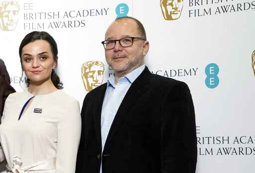 FILE - In this Wednesday, Jan. 9, 2019 file photo, BAFTA Chair of the Film Committee Marc Samuelson poses for photographers next to actor Hayley Squires in London. The British Academy of Film and Television Arts promised to change after nominations for the 2020 awards were announced last January. No women were nominated as best director for the seventh year running, and all 20 nominees in the lead and supporting performer categories were white.