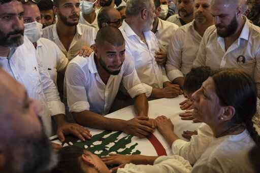 Relatives and friends of 23-year-old Ralph Malahi, one of the firefighters killed in the Aug. 4 explosion that hit the seaport, mourn during his funeral in Beirut, Lebanon, Saturday, Aug. 15, 2020. (AP Photo/Felipe Dana)