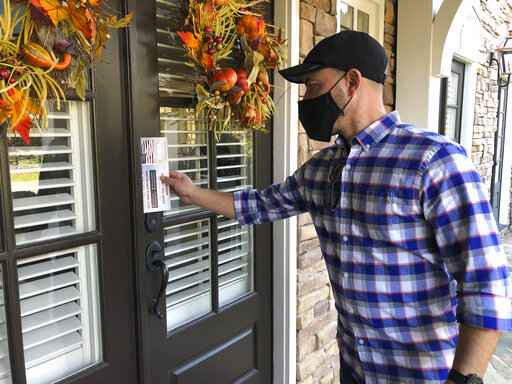 Garrett Bess, vice president of government relations and communications for the conservative activist group Heritage Action For America, leaves information at a residence in a subdivision in Milton, Ga., Friday, Nov. 20, 2020. Bess and a colleague were going door-to-door to encourage people to vote for the conservative candidates in Georgia's Jan. 5 runoff elections for U.S. Senate. The two Georgia races will decide which party controls the Senate, and that has infused voter turnout efforts by the parties and outside groups with new urgency. (AP Photo/Sudhin Thanawala)