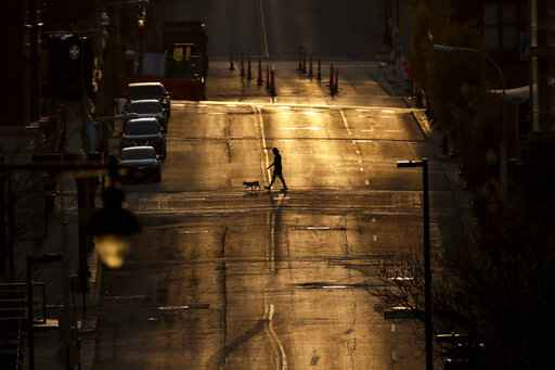 A man walks a dog on an empty downtown street as the sun sets Wednesday, April 1, 2020, in Kansas City, Mo. (AP Photo/Charlie Riedel)