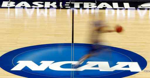 FILE - In this March 14, 2012, file photo, a player runs across the NCAA logo during practice in Pittsburgh before an NCAA tournament college basketball game. A court decision the NCAA says will hurt college sports by allowing student-athletes to be paid