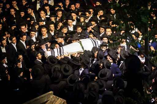 Ultra-Orthodox Jewish men carry the body of Yossi Kohn, 21, from Cleveland, Ohio, who died during Lag BaOmer celebrations at Mt. Meron in northern Israel, at his funeral in Jerusalem, Sunday, May 2, 2021. A stampede at a religious festival attended by tens of thousands of ultra-Orthodox Jews in northern Israel killed dozens of people and injured about 150 early Friday, medical officials said. It was one of the country's deadliest civilian disasters. (AP Photo/Oren Ben Hakoon)
