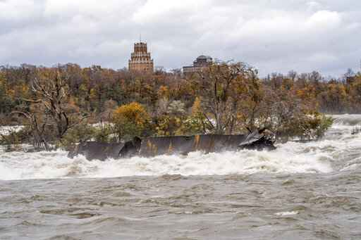 In this Nov. 1, 2019 photo provided by Niagara Parks, a century-old barge has shifted slightly in the St. Lawrence River above the Niagara Falls in Ontario, Canada. Parks officials are monitoring the iron scow, which grounded in 1918, that briefly broke loose during a storm last week. (Chris Giles/Niagara Parks via AP)