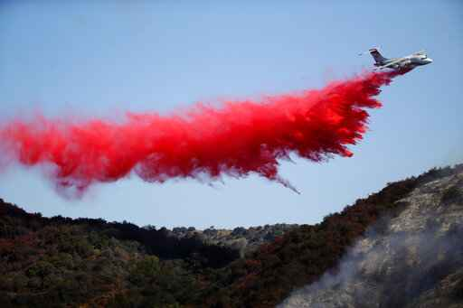 A plane drops retardant as the Getty fire burns on Mandeville Canyon Monday, Oct. 28, 2019, in Los Angeles. (AP Photo/Marcio Jose Sanchez)