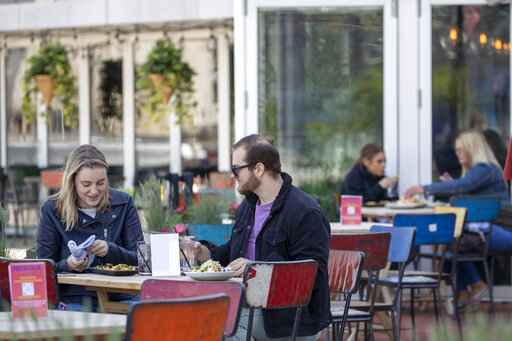 Emily Black, left, and Adam Weinstein have lunch on the outdoor patio of Mexicue restaurant, Wednesday, May 20, 2020, in Stamford, Conn. Restaurants can begin offering service in outdoor dining areas Wednesday as part of the first phase of Connecticut's statewide reopening, including in hard-hit Fairfield County on the New York state line. (AP Photo/Mary Altaffer)