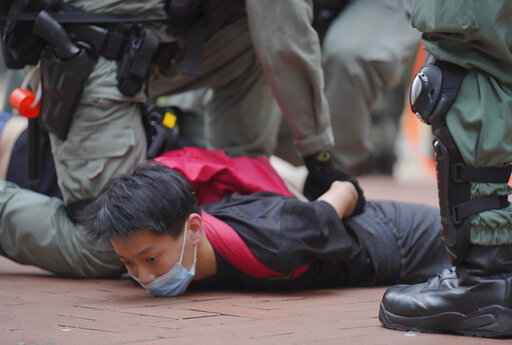 A protester is detained by riot police during a demonstration against Beijing's national security legislation in Causeway Bay in Hong Kong, Sunday, May 24, 2020. Hong Kong police fired volleys of tear gas in a popular shopping district as hundreds took to the streets Sunday to march against China's proposed tough national security legislation for the city. (AP Photo/Vincent Yu)